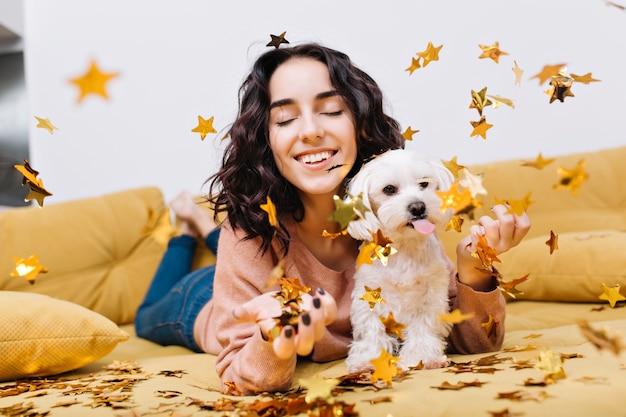 Retrato alegre incrível jovem sorrindo com os olhos fechados em enfeites dourados caindo. relaxando no sofá com animais domésticos, cachorrinho branco, sorrindo, humor alegre, relaxamento