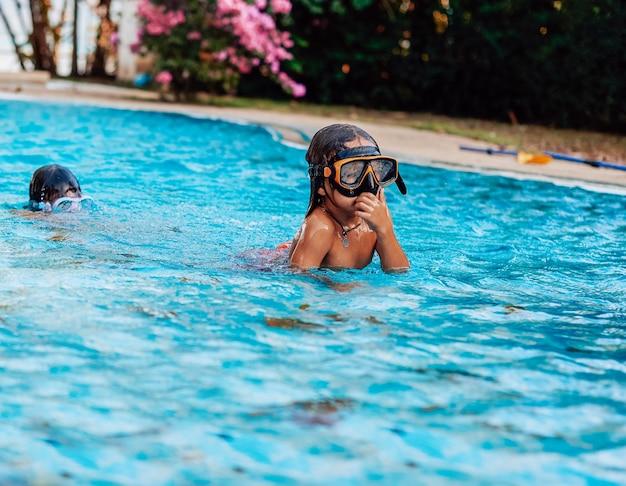 Retrato amigável de duas crianças brincalhonas e alegres que nadam em uma piscina e mergulham na água durante o dia.