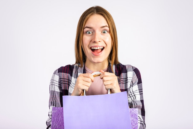 Retrato animado mulher segurando sacos e olhando para a câmera