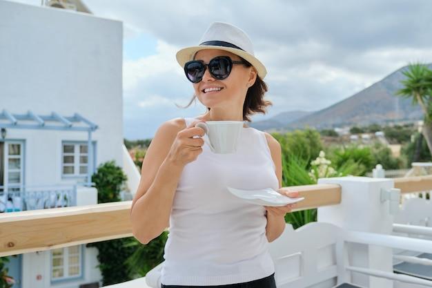 Retrato ao ar livre adulto linda mulher com um copo de bebida, feliz linda mulher madura descansando em um restaurante em um dia ensolarado de verão