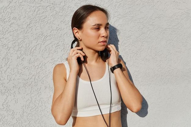 Retrato ao ar livre da bela jovem adulto feminino vestindo top branco, ouvindo música durante o treinamento, mantendo as mãos nos fones de ouvido, olhando para longe com expressão facial pensativa.