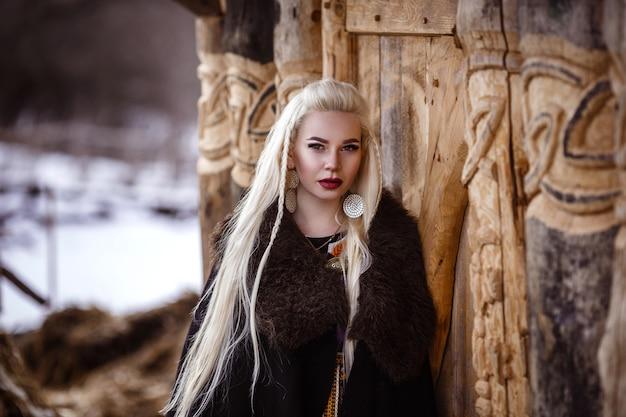Retrato ao ar livre da bela mulher furiosa guerreira escandinava ruiva com roupas tradicionais