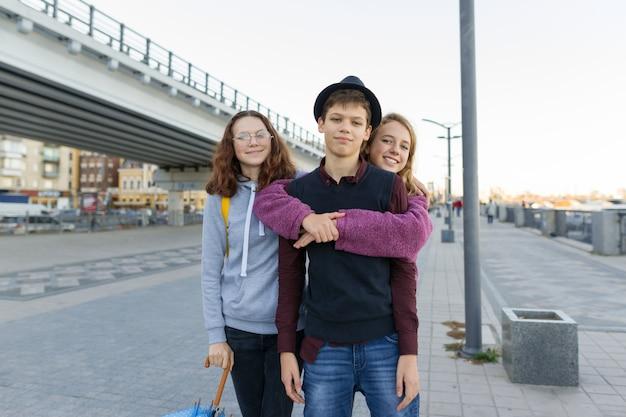 Retrato ao ar livre da cidade de três amigos adolescentes meninos e meninas
