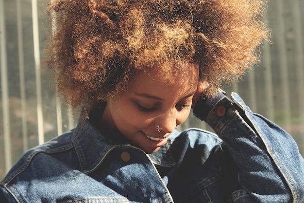 Retrato ao ar livre da elegante garota africana com corte de cabelo afro, olhando para baixo com uma expressão alegre e despreocupada.