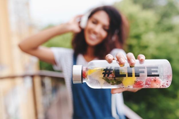 Retrato ao ar livre da garota negra sorridente em uma camisa branca com uma garrafa na mão em primeiro plano
