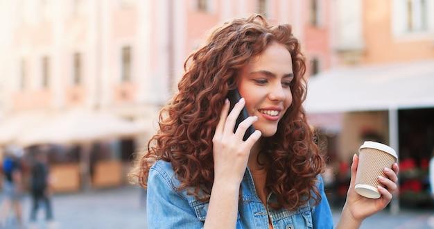 Retrato ao ar livre da jovem elegante, vestindo roupas da moda, sorrindo alegremente e conversando ...