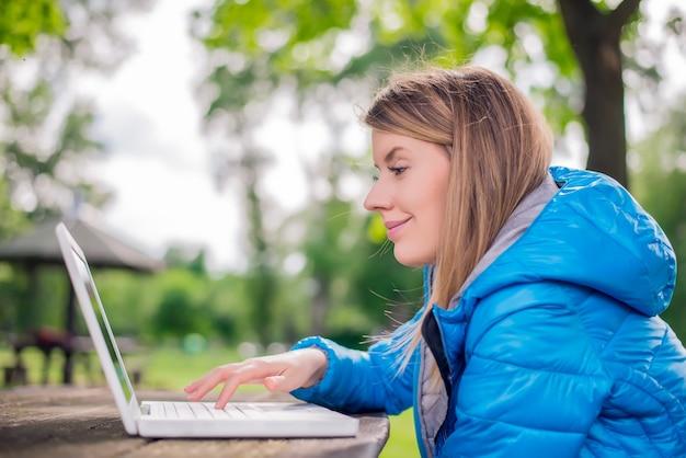 Retrato ao ar livre da jovem mulher no parque com laptop.