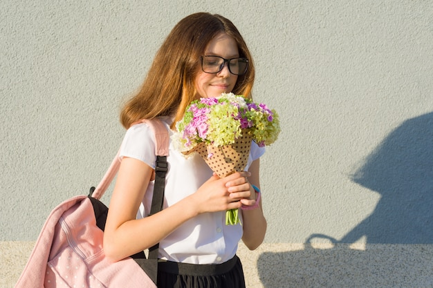 Retrato ao ar livre da menina com buquê de flores.