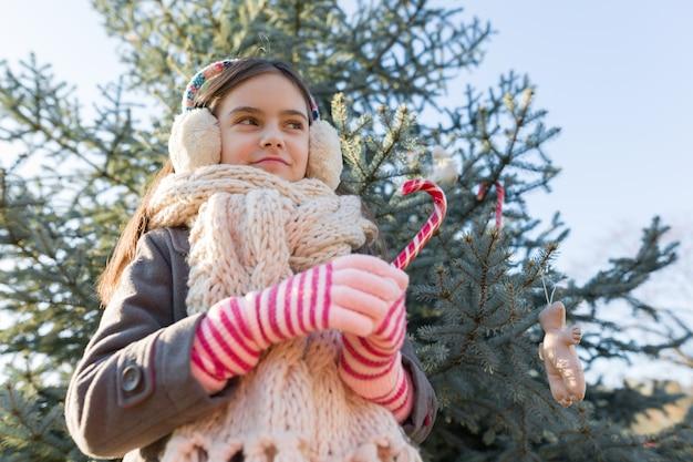 Retrato ao ar livre da menina perto da árvore de natal
