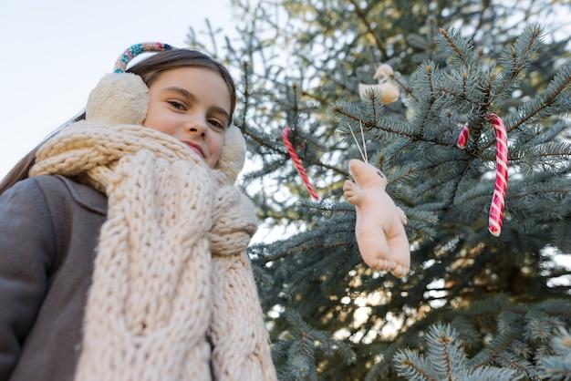Retrato ao ar livre da menina perto da árvore de natal.