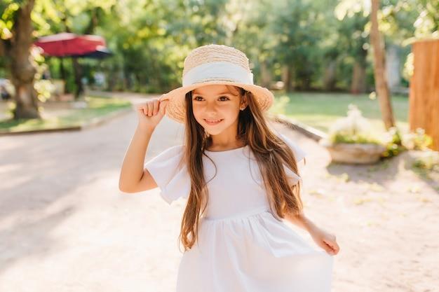 Retrato ao ar livre da menina sorridente com cabelo escuro longo e reto, caminhando no parque na manhã ensolarada. criança alegre do sexo feminino com chapéu de palha e vestido branco, aproveitando as férias, passar o tempo na rua.
