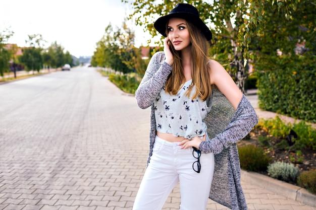 Retrato ao ar livre da moda de uma jovem mulher loira muito sensual posando na zona rural em tempo de outono, vestindo elegante hipster casual deve e chapéu, cores vintage suaves, andando sozinho.