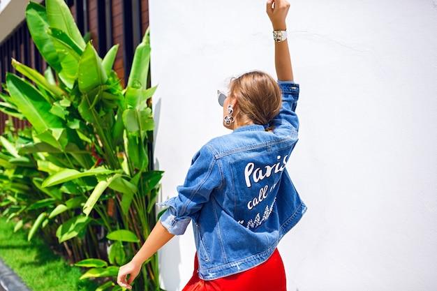 Retrato ao ar livre da moda de uma mulher loira deslumbrante, usando um vestido de noite elegante de luxo, óculos de sol do salário. e jaqueta hipster, folhas tropicais no fundo.