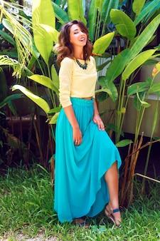 Retrato ao ar livre da moda de uma mulher morena linda e sensual, com incríveis cabelos longos, qualquer brilhante maquiagem, posando perto de plantas exóticas no dia de verão, usando colar e vestido de seda brilhante de luxo.