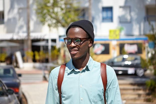 Retrato ao ar livre da moda jovem estudante afro-americana em roupas elegantes, andando em ambiente urbano, aproveitando a manhã ensolarada enquanto vai para a faculdade a pé, tendo expressão alegre no rosto