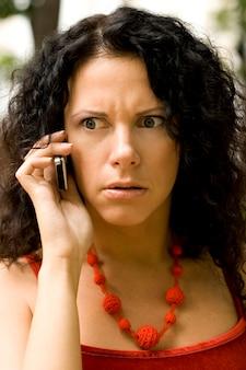 Retrato ao ar livre da mulher no telefone recebendo más notícias