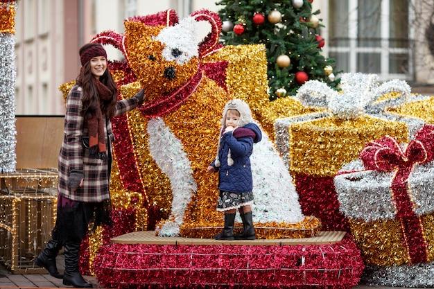 Retrato ao ar livre da mulher sorridente e menina em decorações de natal na rua da cidade