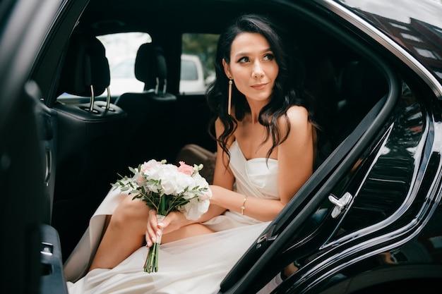 Retrato ao ar livre da noiva feliz muito jovem. noiva sorridente elegante vestido branco segurando boquet de flores e olhando para fora do carro no dia do casamento