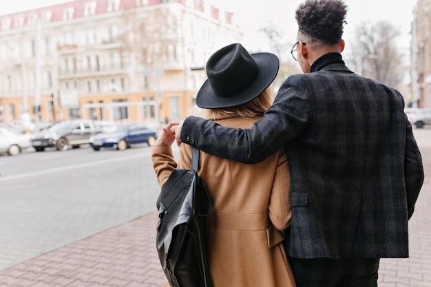 Retrato ao ar livre da parte de trás do homem africano em terno xadrez, abraçando suavemente a namorada loira. menina com casaco bege, apreciando a vista da cidade durante o encontro.