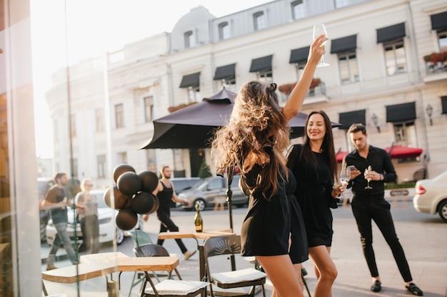 Retrato ao ar livre dançando modelo feminino bronzeado com cabelo comprido balançando