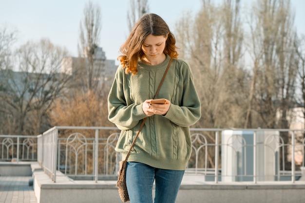 Retrato ao ar livre de adolescente andando e mandando mensagens no celular