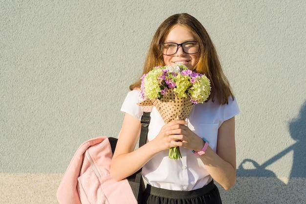 Retrato ao ar livre de adolescente com buquê de flores