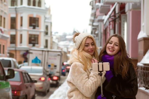 Retrato ao ar livre de amigas bonitas sorridentes fazendo selfie na rua em dia de inverno