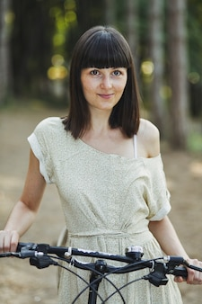 Retrato ao ar livre de atraente jovem morena de bicicleta.
