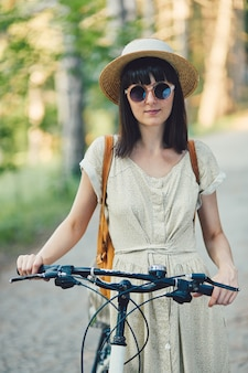 Retrato ao ar livre de atraente jovem morena de chapéu em uma bicicleta.