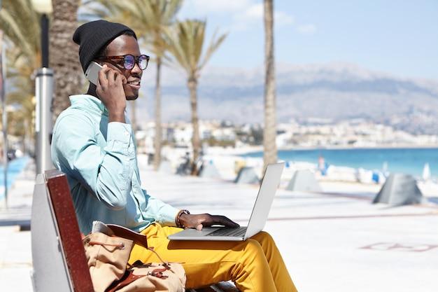 Retrato ao ar livre de bonito homem africano vestindo roupas elegantes e óculos relaxantes no banco da praia do hotel durante as férias no país tropical, usando o computador notebook e falando no celular