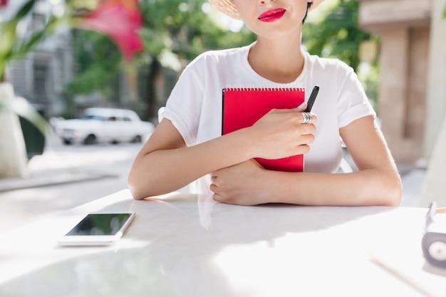 Retrato ao ar livre de close-up de uma senhora romântica de camisa branca segurando um diário vermelho e sorrindo