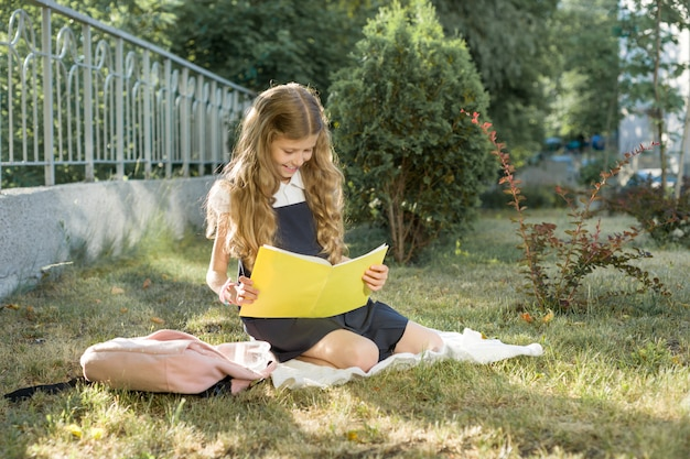 Retrato ao ar livre de colegial sentado na grama lendo caderno