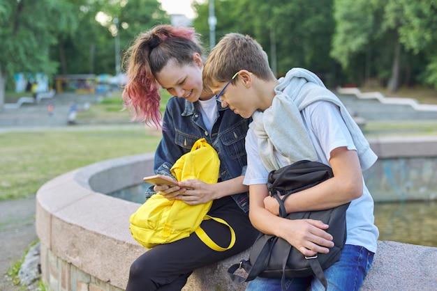 Retrato ao ar livre de dois adolescentes conversando com smartphone