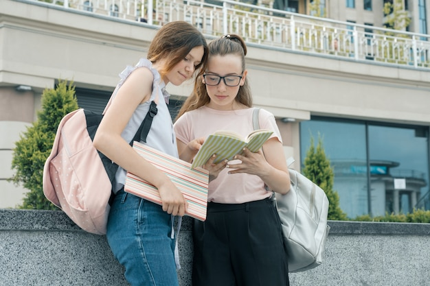 Retrato ao ar livre de dois estudantes de meninas bonitas com mochilas