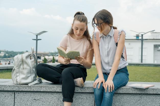 Retrato ao ar livre de dois estudantes de meninas bonitas