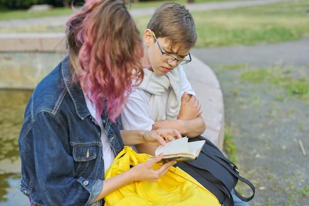Retrato ao ar livre de dois estudantes falantes de adolescentes