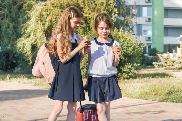 Retrato ao ar livre de duas alunas com mochilas em uniformes escolares