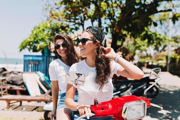 Retrato ao ar livre de duas belas jovens vestidas com camisetas brancas e óculos escuros, drenando ao redor da ilha ao sol e se divertindo, elas estão sorrindo e conversando