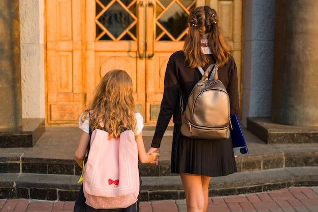 Retrato ao ar livre de duas meninas, ir para a escola