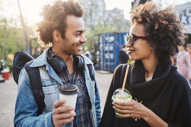 Retrato ao ar livre de duas pessoas afro-americanas fofas rondando o parque, bebendo café, rindo e conversando.