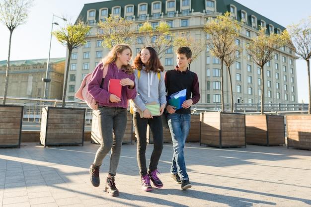 Retrato ao ar livre de estudantes adolescentes com mochilas andando e conversando.