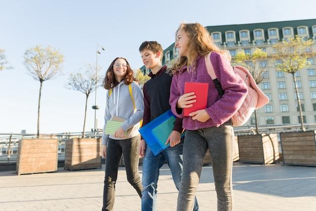 Retrato ao ar livre de estudantes adolescentes com mochilas, caminhando e conversando.
