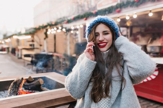 Retrato ao ar livre de excitada menina morena com casaco de lã, aproveitando o fim de semana de inverno em dia quente. foto de uma senhora caucasiana de cabelos compridos com um lindo chapéu azul, posando na rua borrada