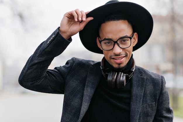 Retrato ao ar livre de feliz homem confiante em traje escuro. menino africano sorridente usa óculos posando com prazer em blur.