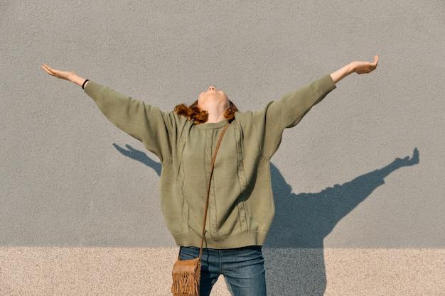 Retrato ao ar livre de feliz menina adolescente com mãos ao alto
