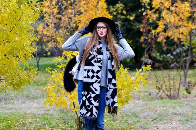 Retrato ao ar livre de garota animada usa aba larga na moda e em pose confiante. mulher jovem e atraente em copos posando em fundo de natureza outono.
