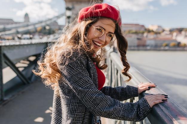 Retrato ao ar livre de glamourosa turista feminina olhando por cima do ombro na ponte