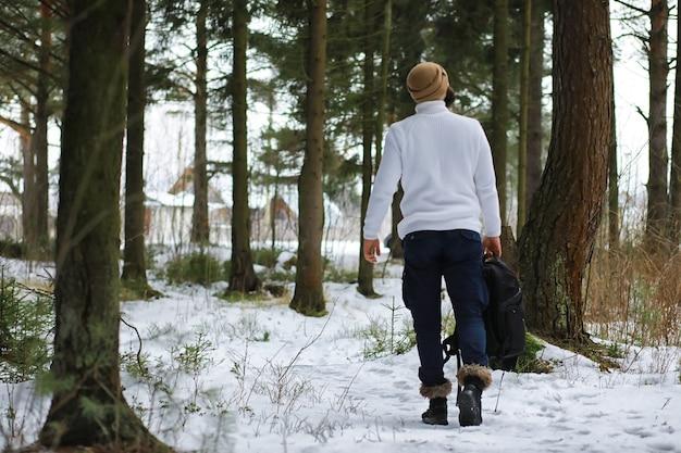 Retrato ao ar livre de homem bonito com casaco e casco. homem barbudo na floresta de inverno.
