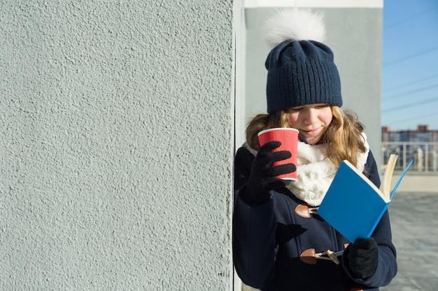 Retrato ao ar livre de inverno da jovem aluna com livro