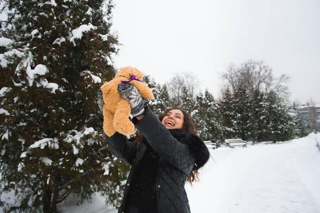 Retrato ao ar livre de inverno de mulher grávida em roupas da moda.